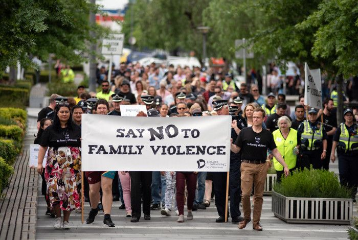 A large group marching with a sign saying 'We say no to family violence'