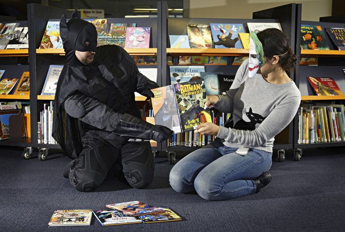 Batman and the Joker cosplay characters fighting over a book