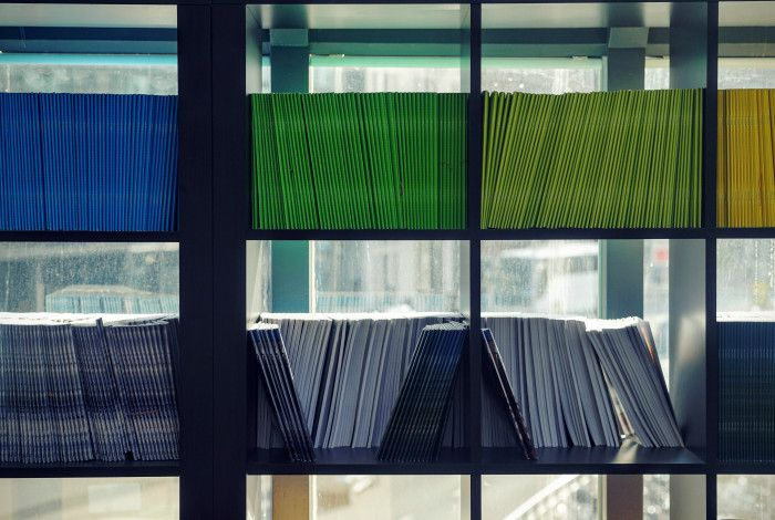 Coloured folders stacked on a book case