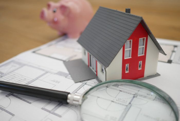 Building plans on a table with a magnifying glass, toy house and piggy bank