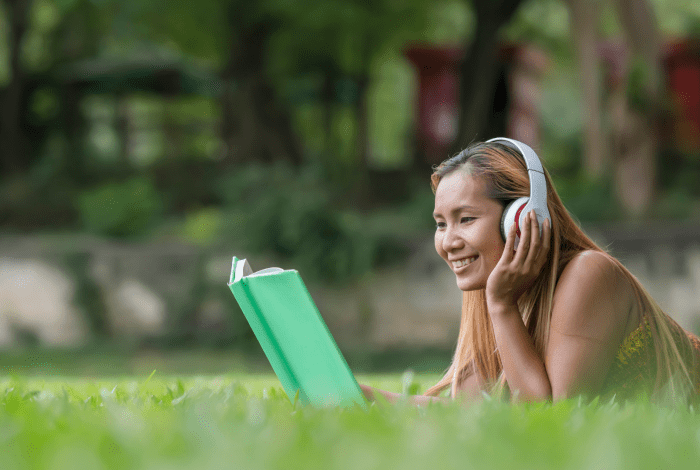girl on grass with headphones